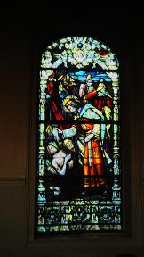 Window in the Saint Louis Cathedral in New Orleans showing the sainted King of France for whom the church is named caring for the sick directly.