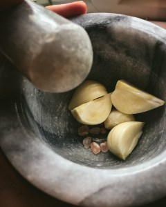 Garlic cloves and salt in a mortar and pestle
