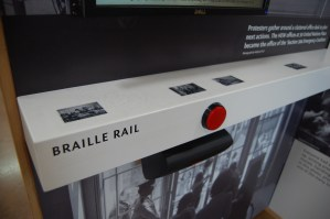 Braille rail detail with red button to activate the video