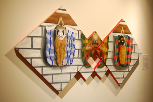 Two large square canvases are turned to be triangles and are joined at their points. Three smaller square canvases, one above the join and two below the join provide more surface for the image. The background is a white brick wall with grey joints, the left and right canvases feature shopping bags with masks in front of them and the top small canvas has an image of an upturned deer head which may be a headdress. The edges of all canvases are painted red.