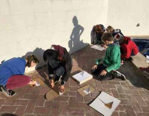 children making cardboard sundials outdoors
