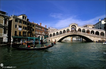 Gondolier passing Grand Canal near Rialto bridge, Venice, Italy