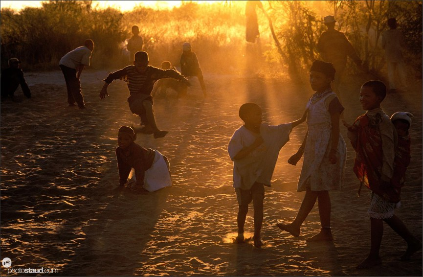 Bushman children playing in the sand, Den/ui village, Bushmanland, Namibia