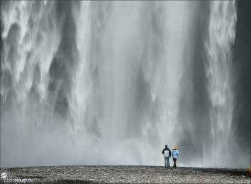 Couple under Skogafoss waterfall, Iceland