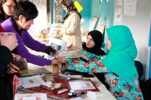 Eine Frau erhält eine Kalligrafie. Foto: Kathrin Erbe
