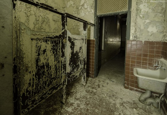 An extremely decaying bathroom in an abandoned insane asylum.