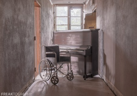 A bracketed HDR photo of a wheelchair and piano taken while urban exploring an abandoned church