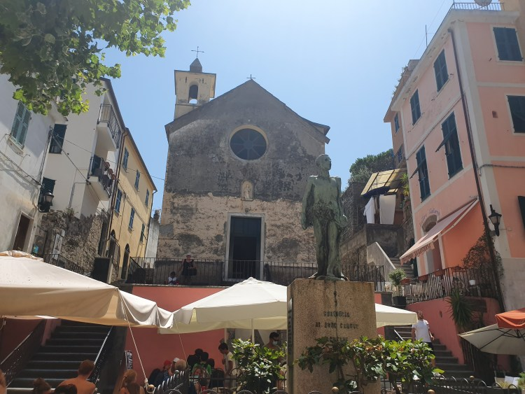 A town square in the village of Corniglia in Cinque Terre, Italy.  A church from the Middle Ages is central to the square.