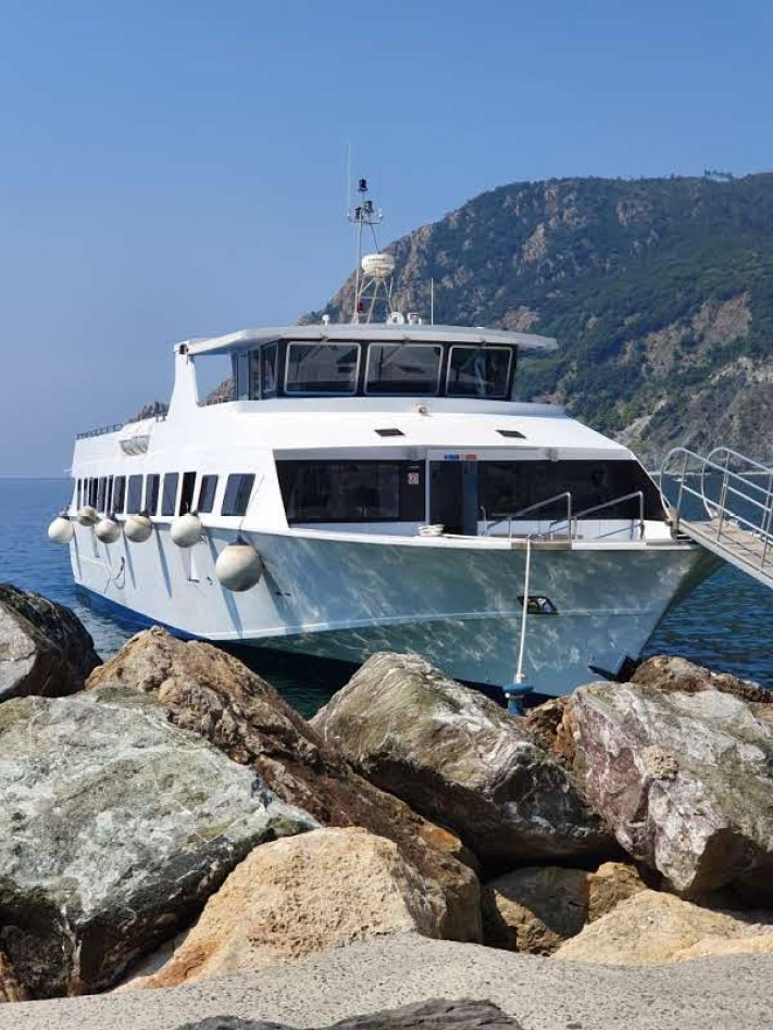 The large white ferry boat in Cinque Terre, Italy docked at the shore in Monterosso.