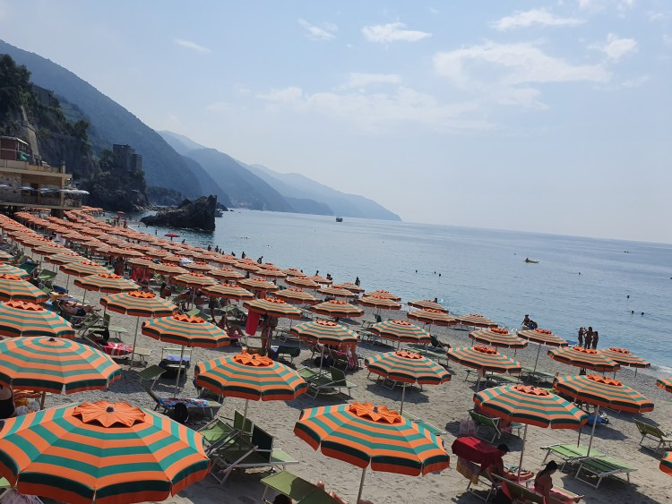 Beach at Monterosso in Cinque Terre, Italy.  Colorful umbrellas and beach chairs are lined up in symmetrical rows.