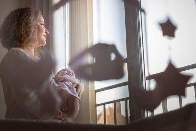 maman regardant par la fenetre portant son bébé dans les bras