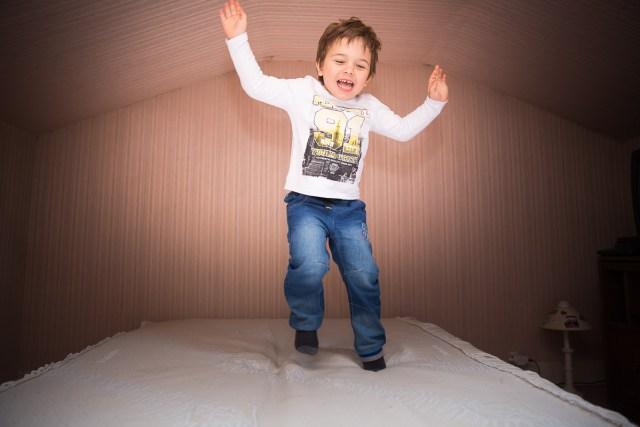 seance session photo a domicile famille belle beau enfant sautant sur le lit