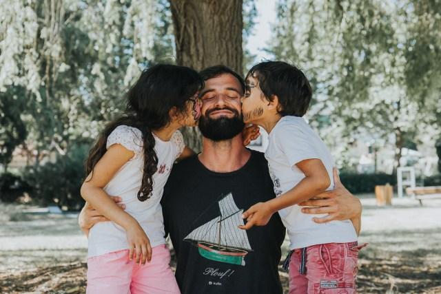 enfants embrassant leur papa sous un arbre séance photo