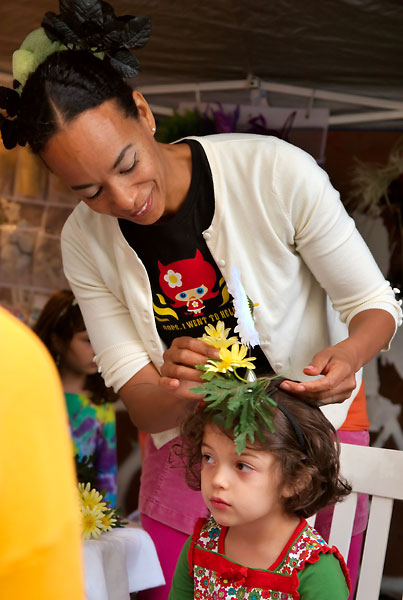 Edisa weaves flowers into a child's hair, 2009, photo by Fred Hatt