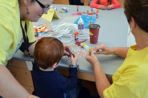 Two adult volunteers help a child make something.