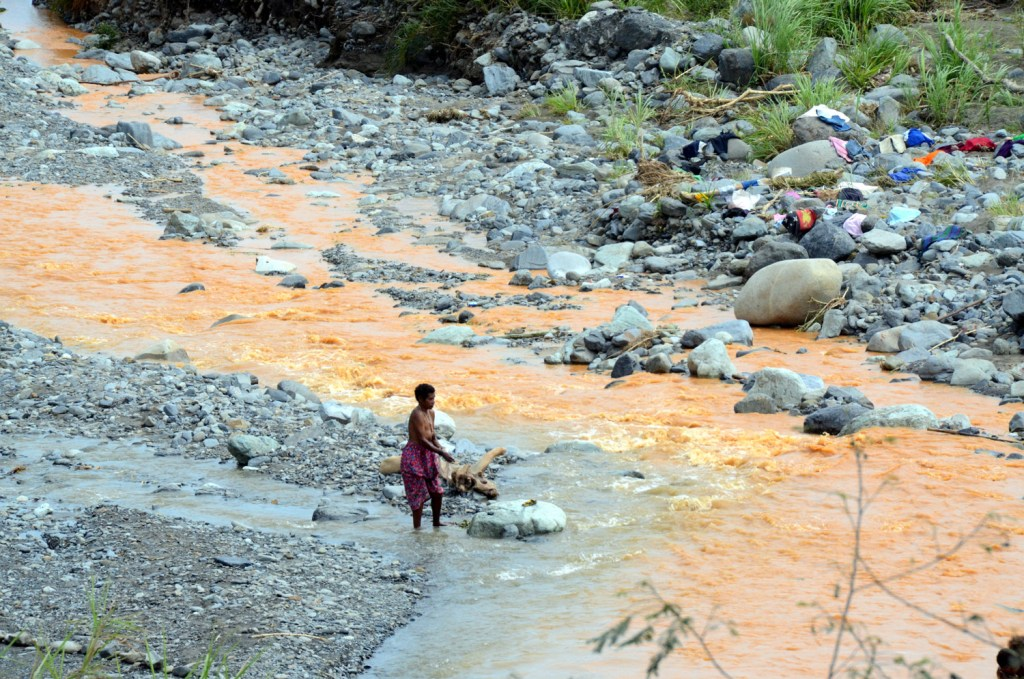 Woman in PNG washing her clothes at the river
