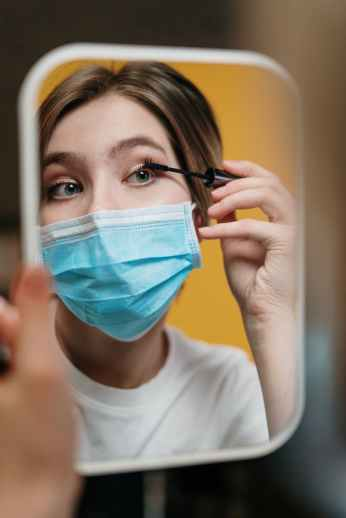 woman putting on mascara despite the outbreak