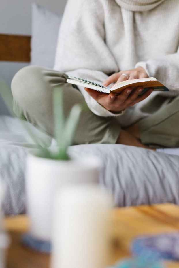 faceless woman reading book on comfortable bed at home