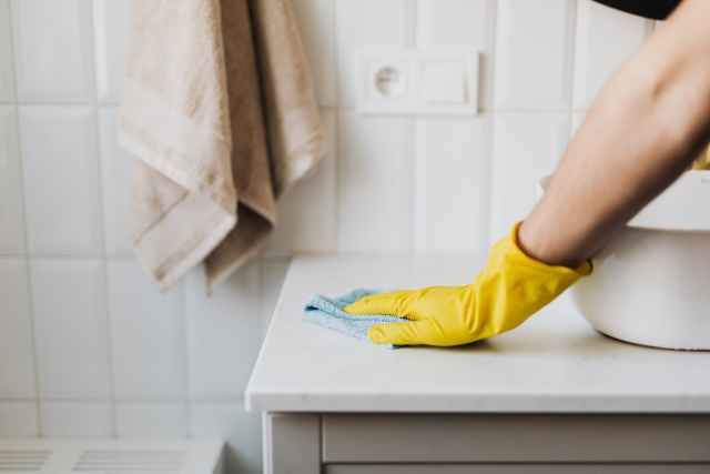 crop housewife cleaning surface near sink