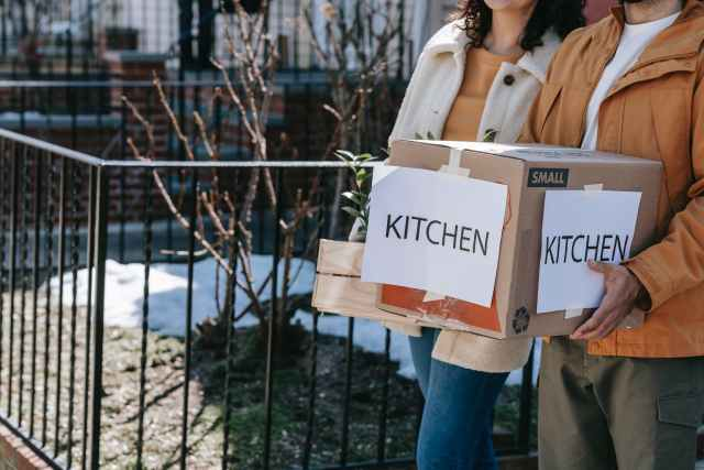 crop photo of man carrying packed kitchen wares in box
