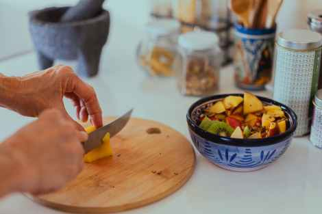 person slicing fruits on a brown wooden chopping board