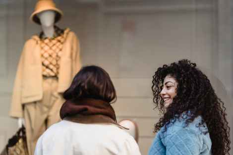 content young ethnic women smiling at street while looking at trendy clothes on mannequin