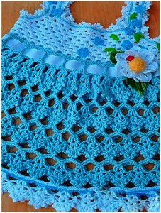 Crochet baby dress in blue color on the table