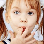 child licking fingers