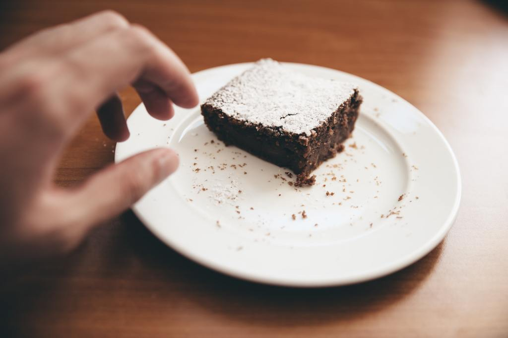 Person reaching for a chocolate brownie on a plate
