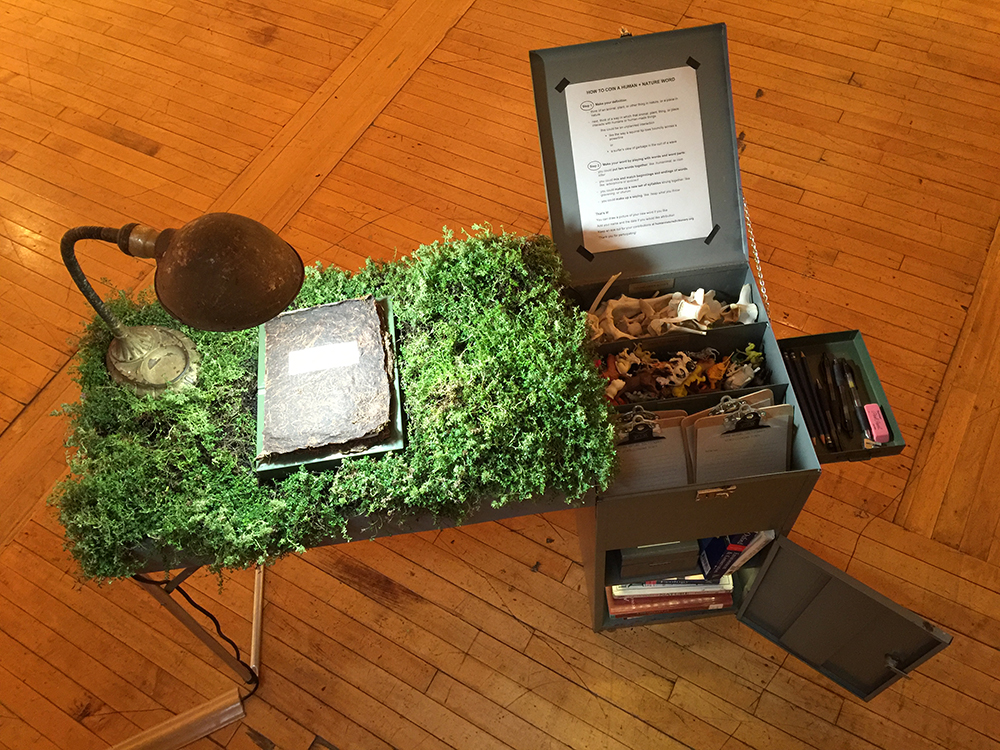 Human Nature Dictionary Field Desk, 2016. Freedom Baird. Steel field desk, vintage chair, living thyme, found deer bones, plastic animals, nature and environmental dictionaries, clipboards, pens, hand-made bioplastic dictionary cover