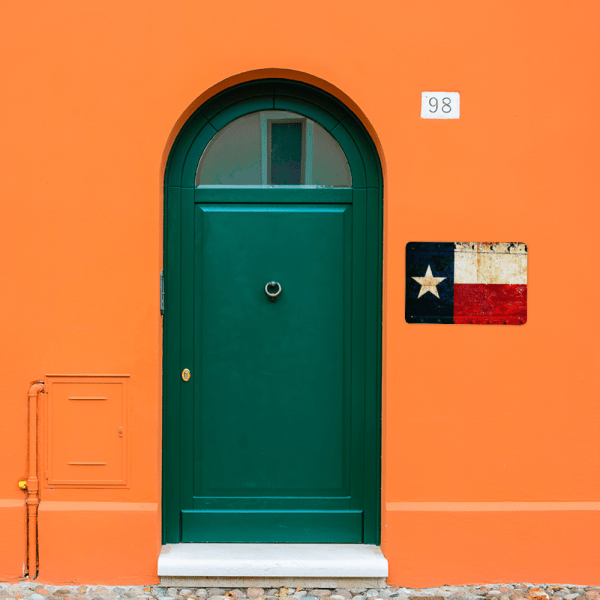 Texas Flag on a rusted, riveted gate and is printed on a metal plaque. Hung outside