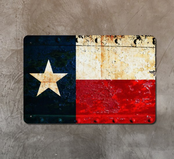 Distressed Texas Flag on rusted riveted gate Print on Metal shown on concrete wall