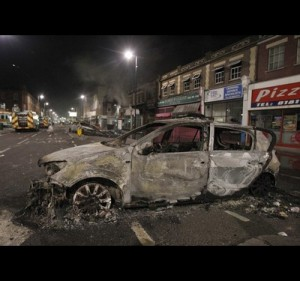 A burnt police car is seen on a street in Tottenham
