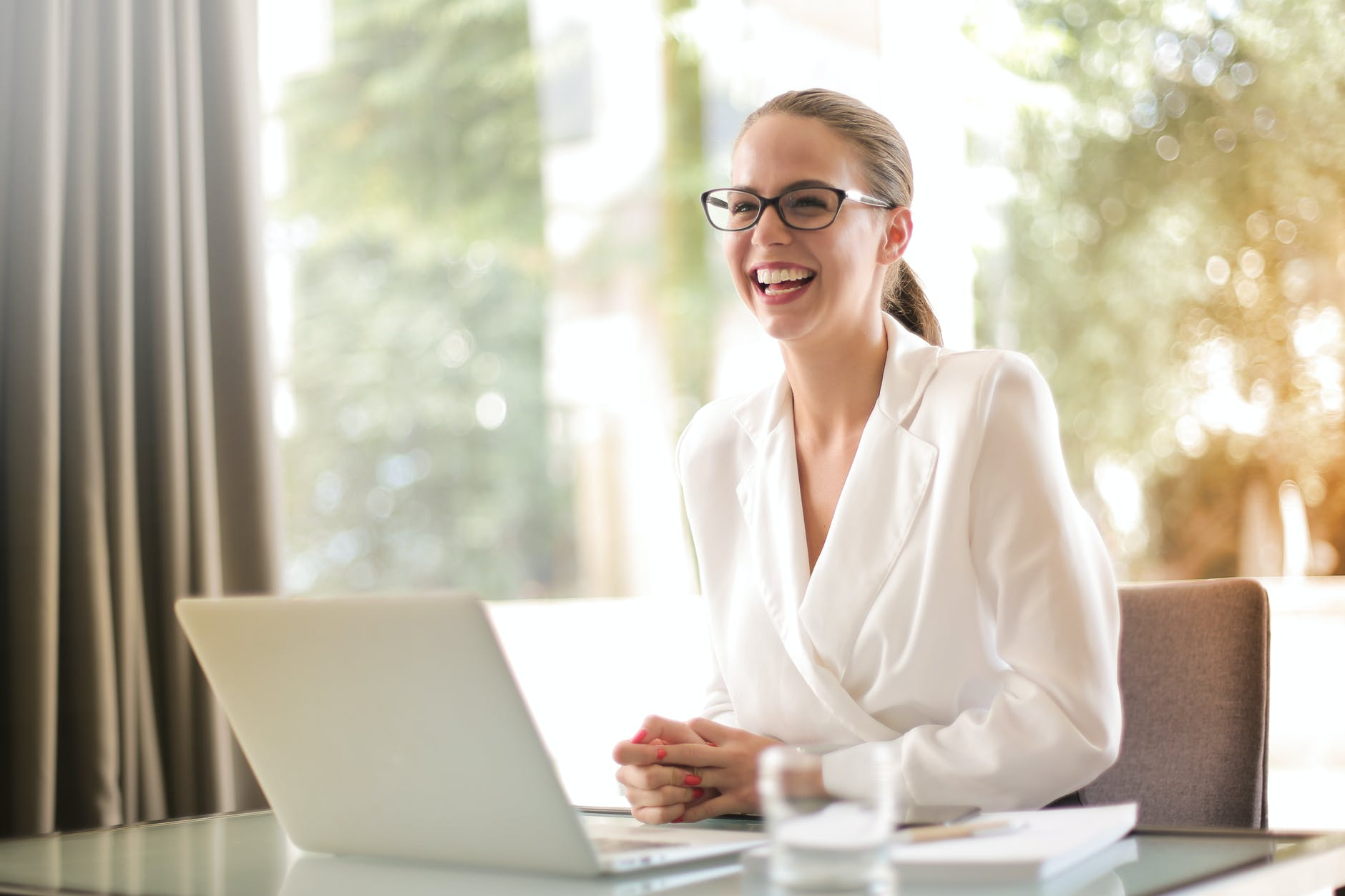 FIRE Movement. laughing businesswoman working in office with laptop