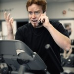 A man on an exercise bike and talking on his cell phone at the same time.