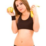 A woman in workout gear holding an apple in one hand and a banana in the other.