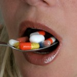 A woman eating a spoon full of vitamin pills.