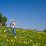 A woman running in a sunny meadow.