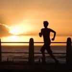A woman running towards a sunset.