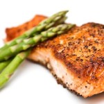 A portion of grilled salmon topped with asparagus.