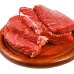 Raw fillet steak on a wooden plate.