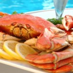 A cooked crab on a platter by a pool.
