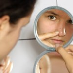 A woman with a spot examining it in the mirror.
