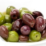 A selection of black and green olives on a white plate.