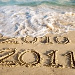 A beach with 2010 and 2011 written on the sand.