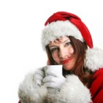 A woman in a Santa hat with a hot drink.