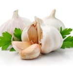 Three cloves of garlic with some parsley.