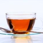 A glass cup of black tea on a glass saucer.