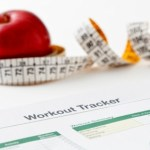 An apple and a tape measure next to a workout tracker sheet.