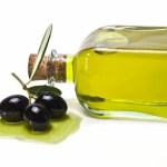 3 olives next to a glass bottle of olive oil.
